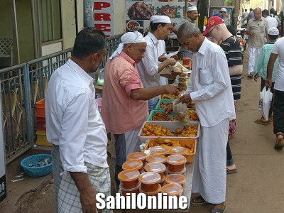 People buying baje, samosa and other snacks getting ready for iftaar on the first day of Ramzan